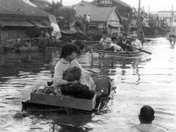 伊勢湾台風の直後、肩までつかる水の中を筏を押して避難する人たち=1959年9月29日、名古屋市南区で